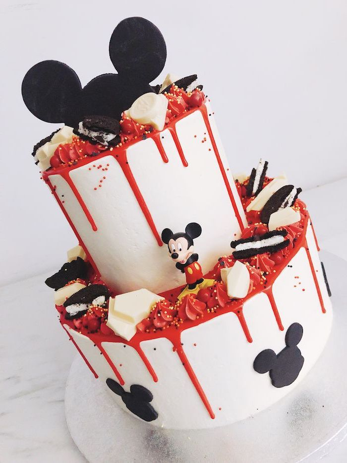 two tier cake, covered with white fondant, mickey mouse cake decorations, decorated with red fondant, dripping on the sides