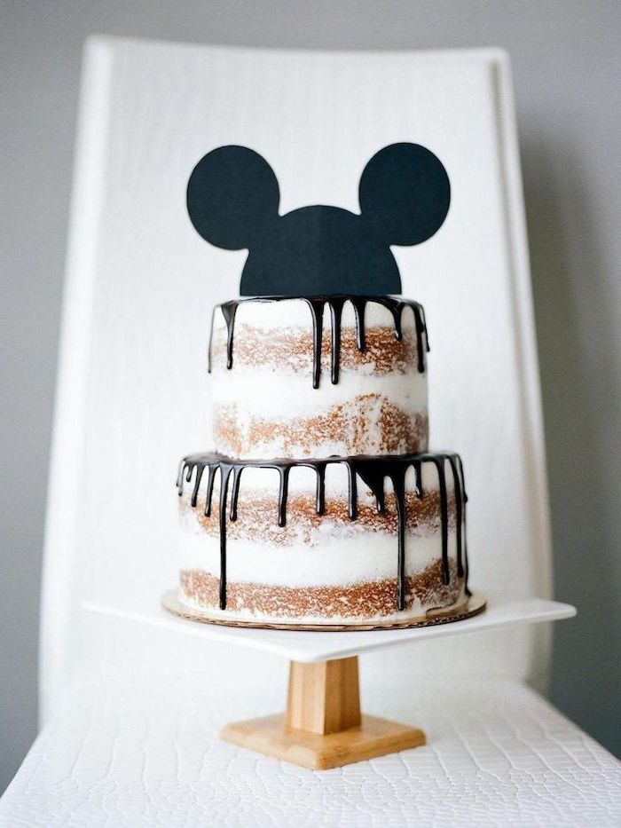 two tier cake, chocolate dripping from the sides, mickey mouse cake decorations, placed on white wooden cake stand