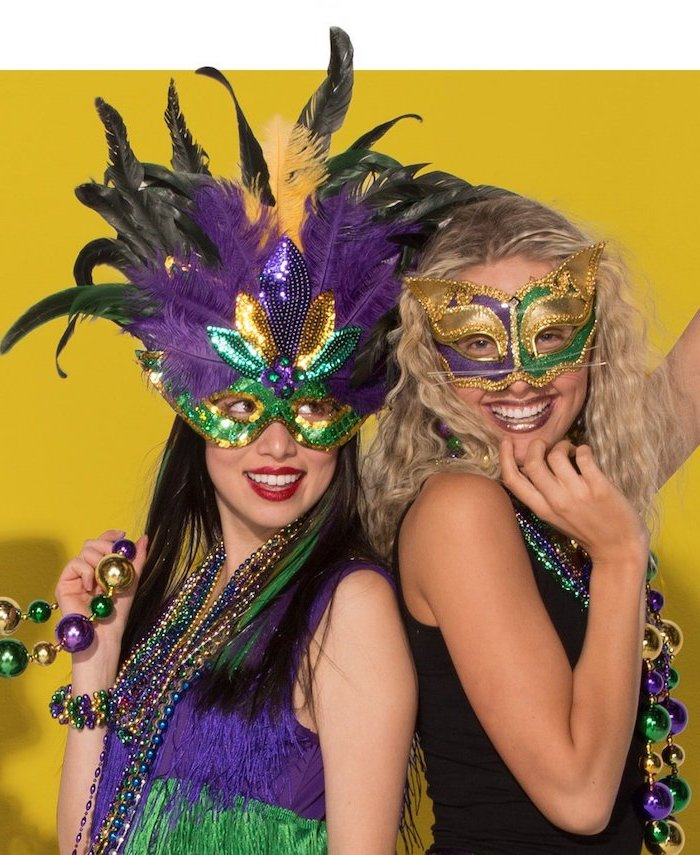 two women smiling, posing for a photograph, wearing different masks, decorated in purple gold and green, mens mardi gras masks