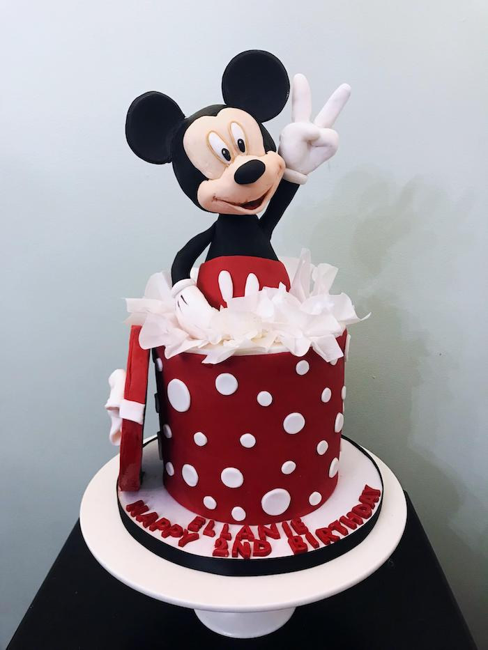 one tier cake, covered with red fondant, placed on white cake stand, mickey cake topper, mickey mouse cake decorations