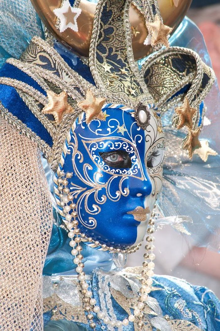 mardi gras mask for men, woman wearing blue satin costume, large jester mask in blue and gold, gold beads around her head
