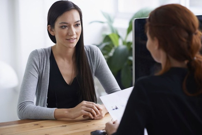 woman with long black hair, sitting at a wooden desk, woman holding a cv, sitting across from her, job interview