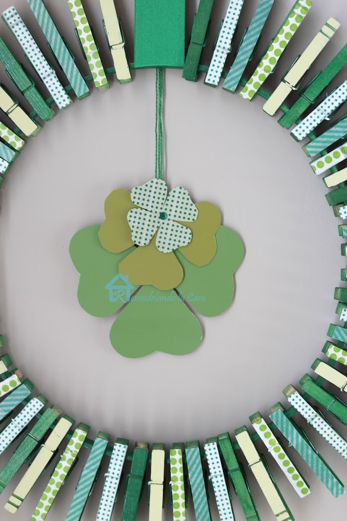 wreath made with clothespins, covered with washi tape with different patterns, st paddy's day, hanging on white wall