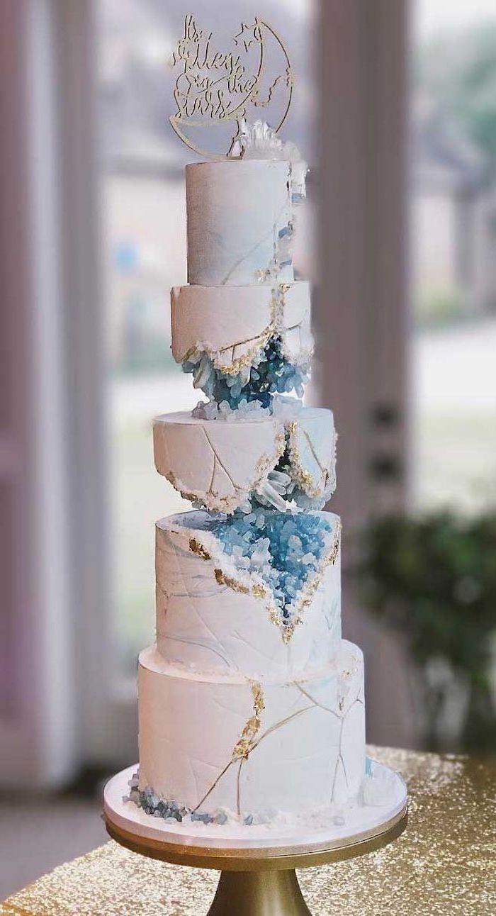 five tier cake, covered with white fondant, decorated with blue rock candy, what is a geode cake, placed on gold cake stand