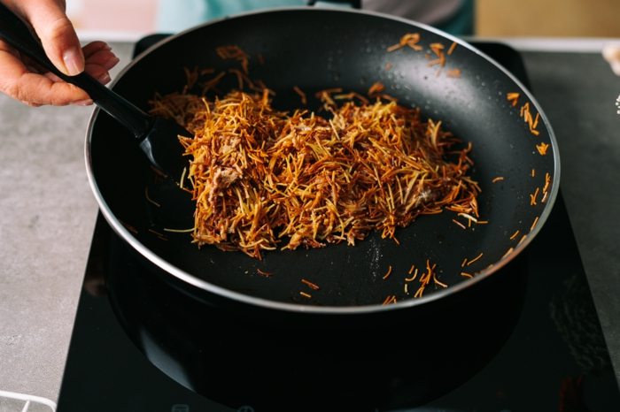angel hair pasta and condensed milk, easter bird nests, cooked in black sauce pan, stirred with black spatula