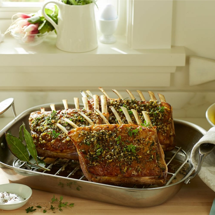 baked lamb with garlic and herbs, easter dinner recipes, baked in a metal baking tray, placed on wooden surface