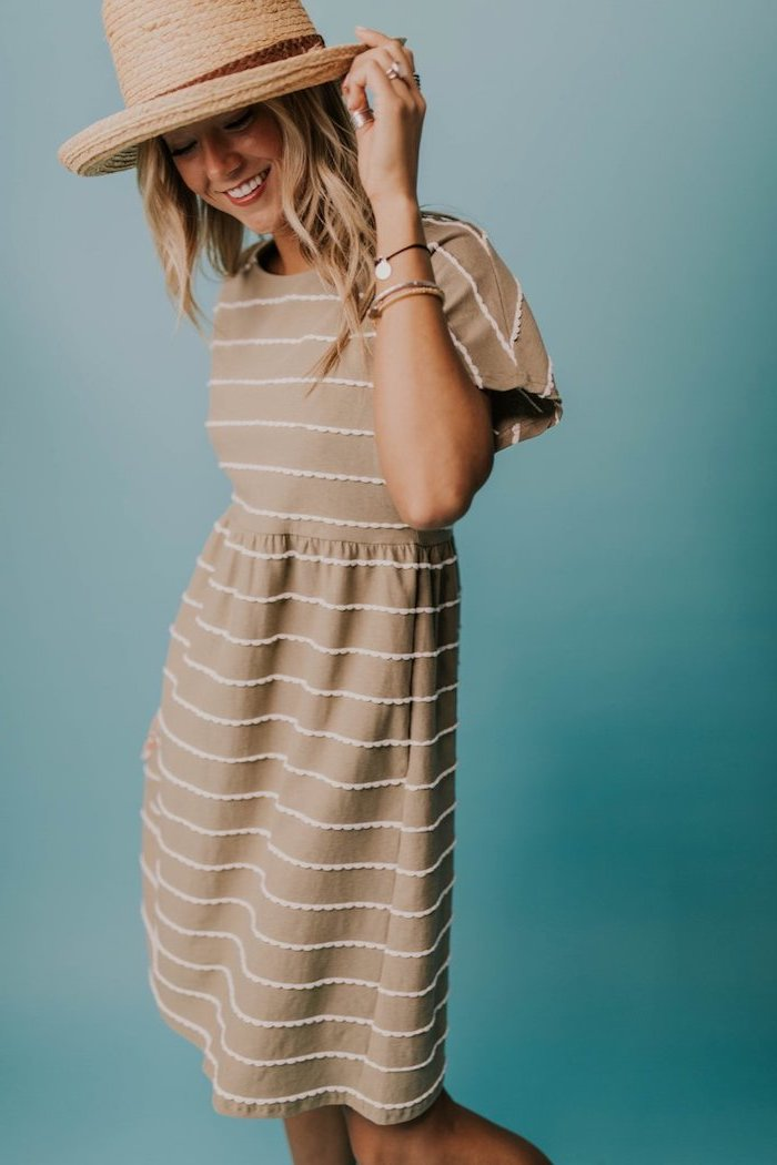 blonde woman wearing a hat on her head, easter dresses for women, wearing a beige dress with white stripes, blue background