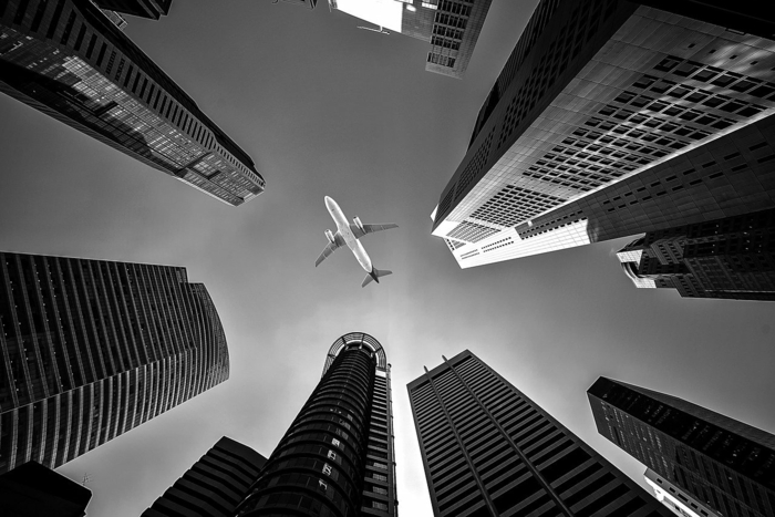 cheapest flights, black and white photo, airplane flying low above tall skyscrapers