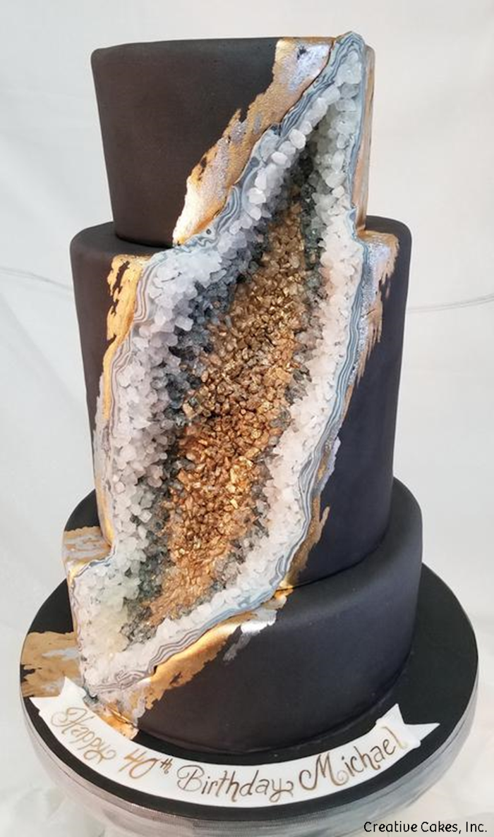three tier cake, covered with black fondant, what is a geode cake, decorated with gold and grey rock candy