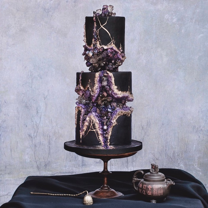 two tier cake, covered with black fondant, geode cake, placed on black cake stand, decorated with purple rock candy