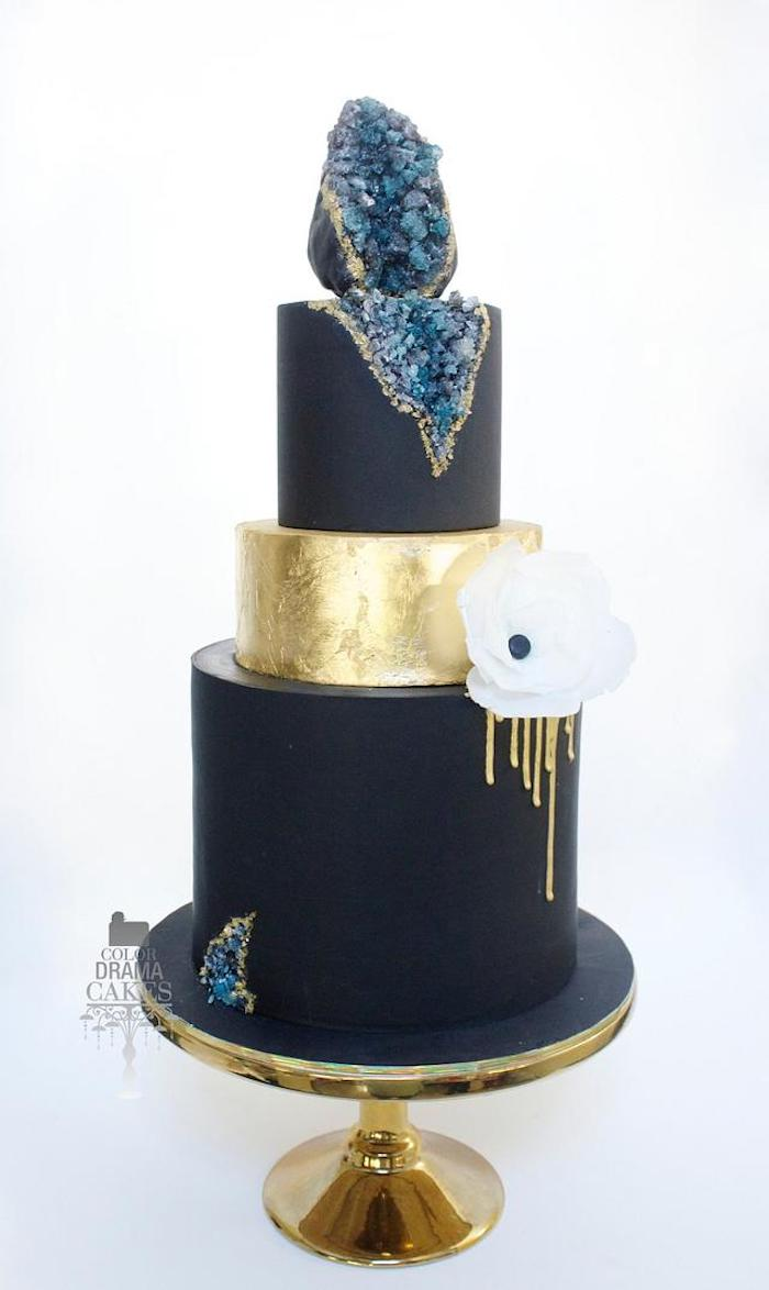 three tier cake, covered with navy blue and gold fondant, placed on gold cake stand, rock candy painted in blue, geode cake