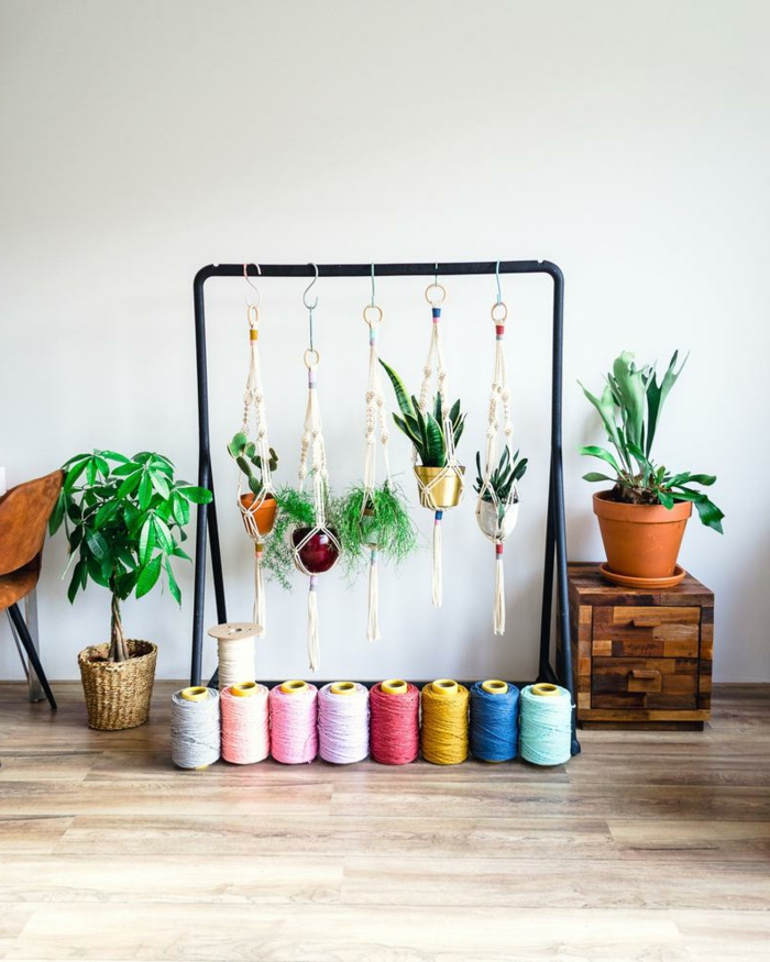 black metal clothing rack, pots with plants hanging from it, how to make a macrame plant hanger, colorful yarn on wooden floor