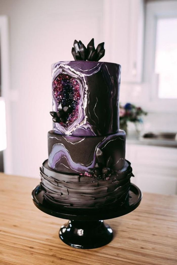 three tier cake, covered in black and purple marble fondant, decorated with black and pink rock candy, geode cake