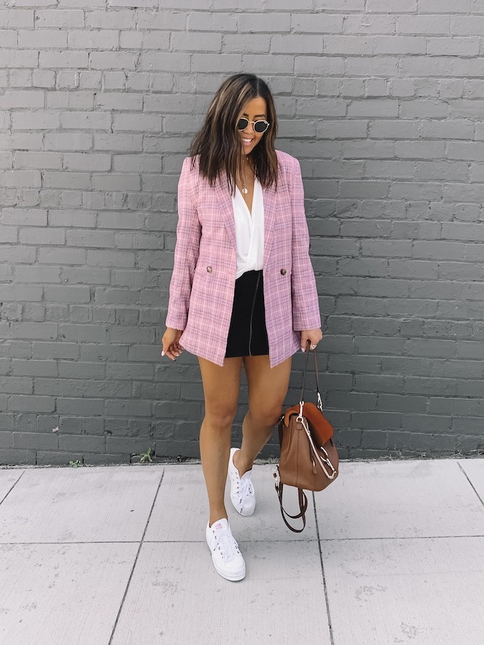 outfit ideas for school, brunette woman wearing black skirt and white top, pink plaid blazer, white sneakers