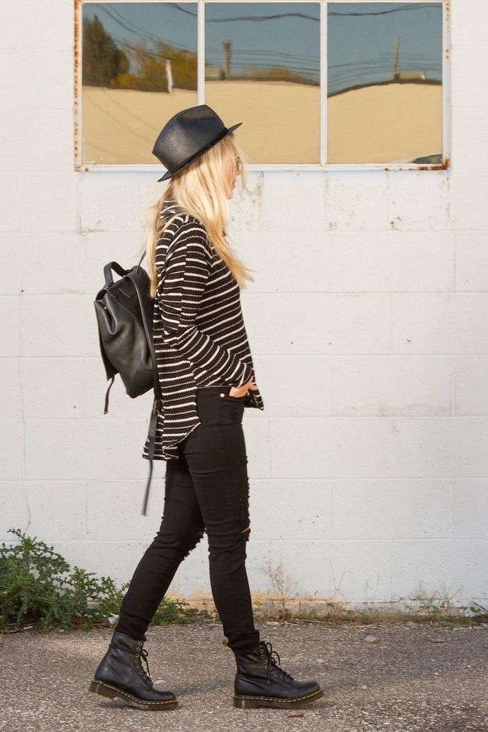 grunge style, blonde woman wearing black jeans, black and white striped blouse, black leather boots hat and backpack, cute outfits for school