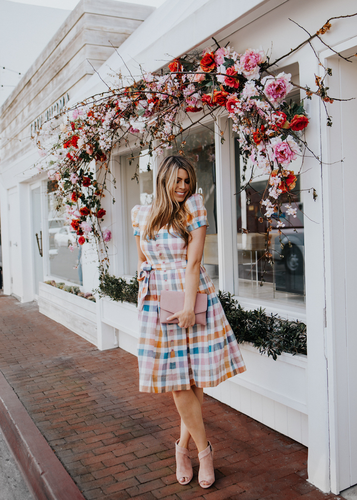 easter dresses for girls, blonde woman wearing a dress with colorful print, nude heels, standing underneath floral wreath