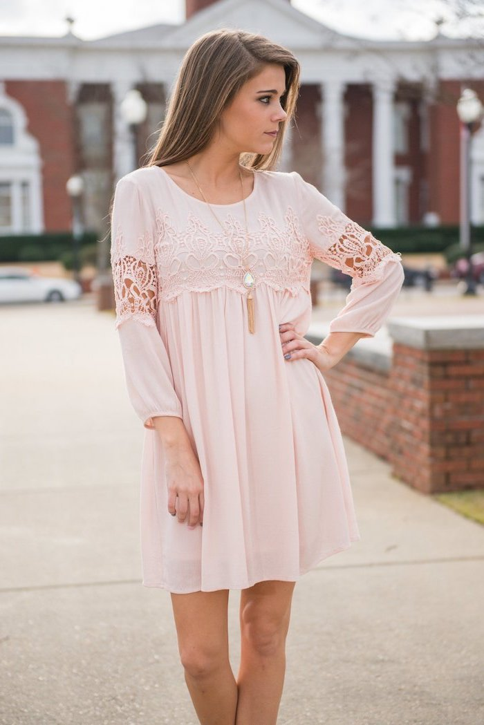 blonde woman standing on a sidewalk, easter dresses for girls, wearing a blush pink dress with lace