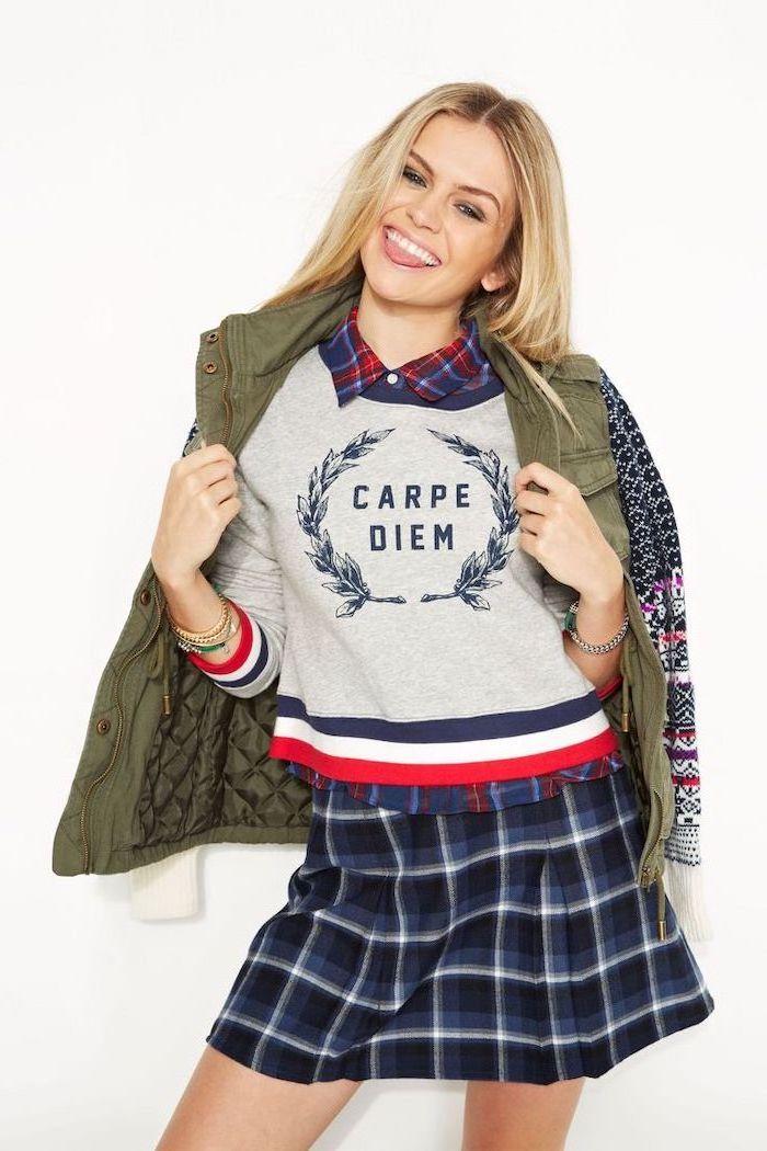 blonde woman wearing grey sweatshirt, plaid skirt and shirt, parka jacket, cute fall outfits, carpe diem sweatshirt