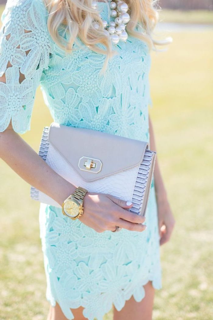 blonde woman wearing blue lace dress, flowy dresses, white pearl necklace and golden watch, leather clutch bag