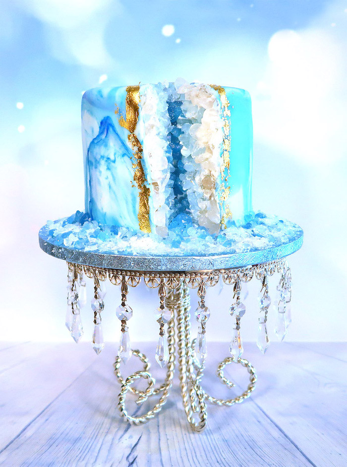 one tier cake, covered with blue and white marble fondant, decorated with rock candy, painted in blue and white, geo cake
