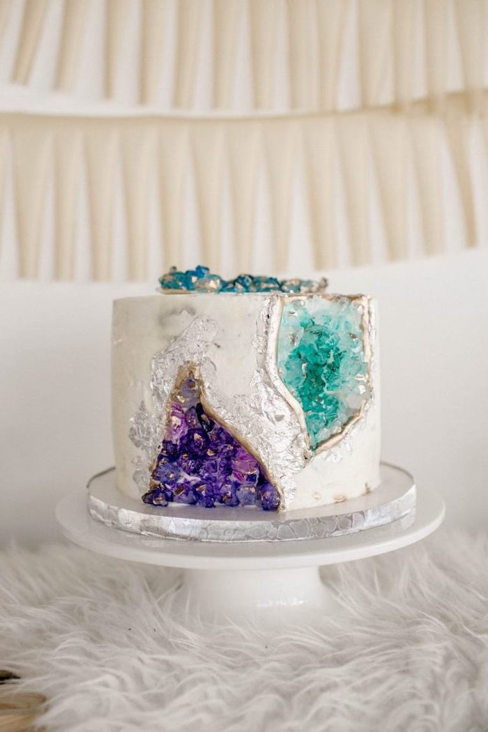 one tier cake, covered with white fondant, crystal cake, decorated with turquoise and purple rock candy, placed on white cake stand