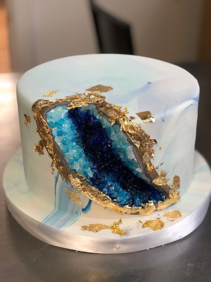 dark blue and turquoise rock candy decoration, gold edible leaves on the side, crystal cake, one tier cake with white fondant