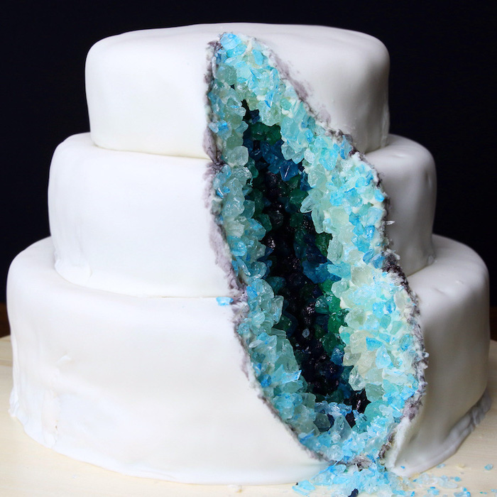 three tier cake, covered with white fondant, decorated with blue and turquoise rock candy, geode wedding cake