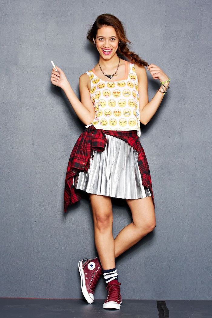 woman with hair in a braid, wearing silver skirt and emoji top, cute fall outfits, red plaid shirt around her waist, red high top converse
