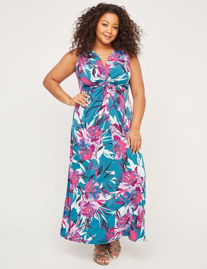 woman with brown curly hair, wearing a long blue dress with floral print, sunflower dress, nude sandals