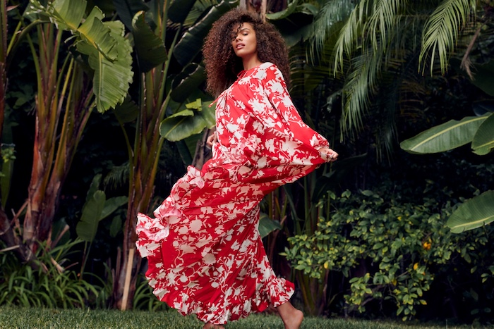 sunflower dress, woman with brown curly hair, wearing a long red dress with floral print, palm trees behind her