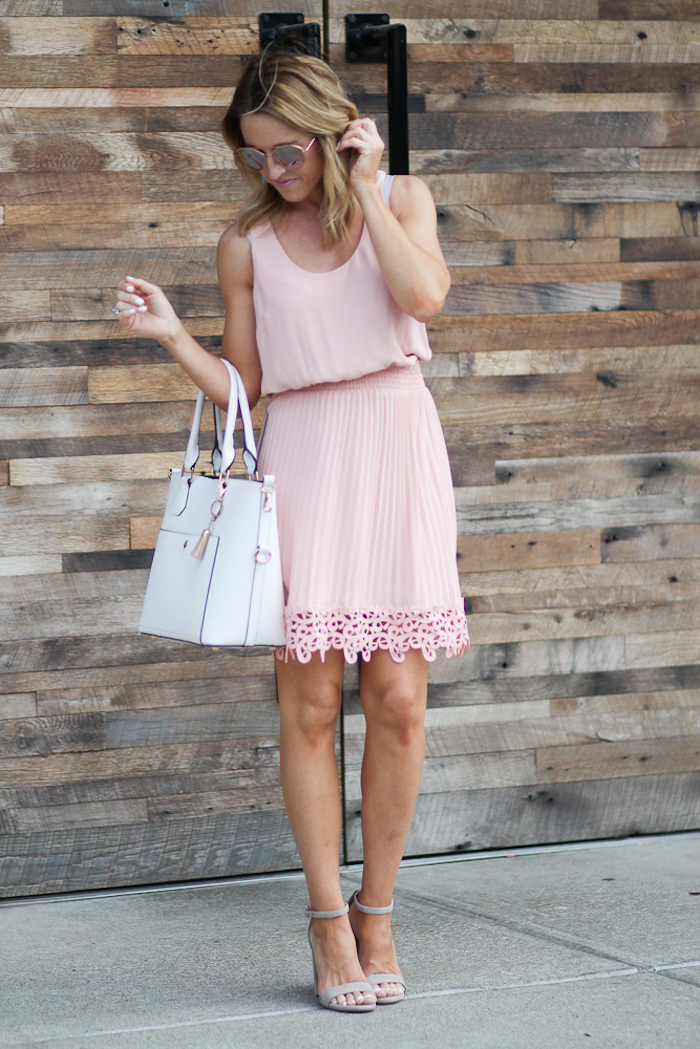 easter outfits, blonde woman wearing blush pink pleated dress, nude sandals and white leather bag
