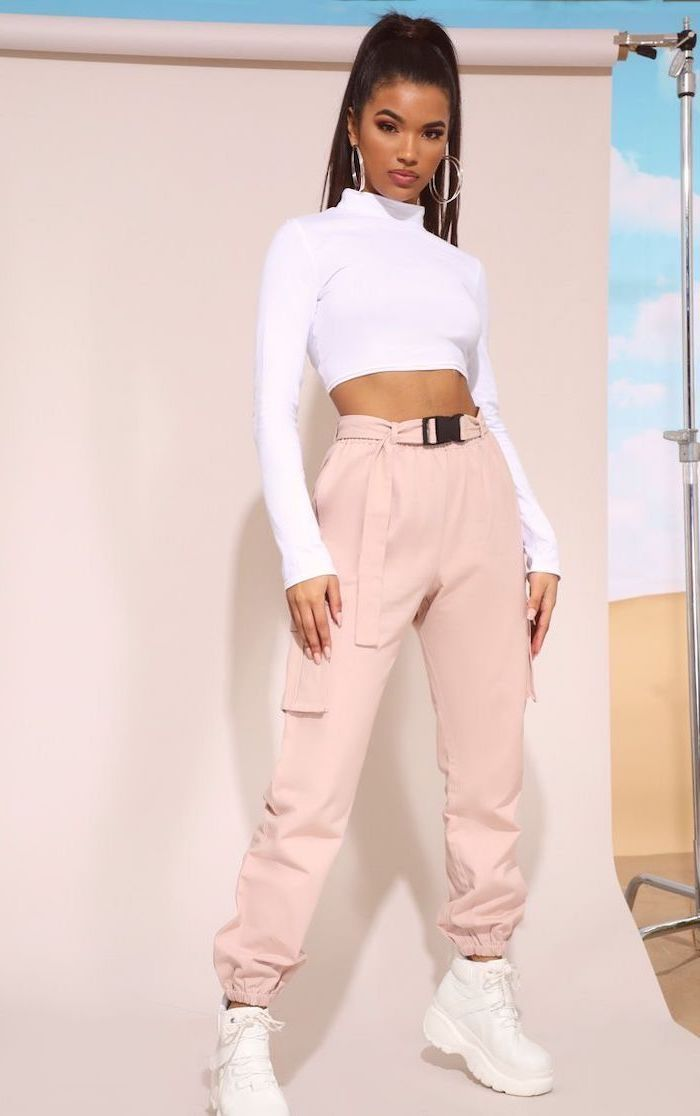 woman with black hair in ponytail, wearing white crop top and blush pink trousers, back to school outfits, white sneakers