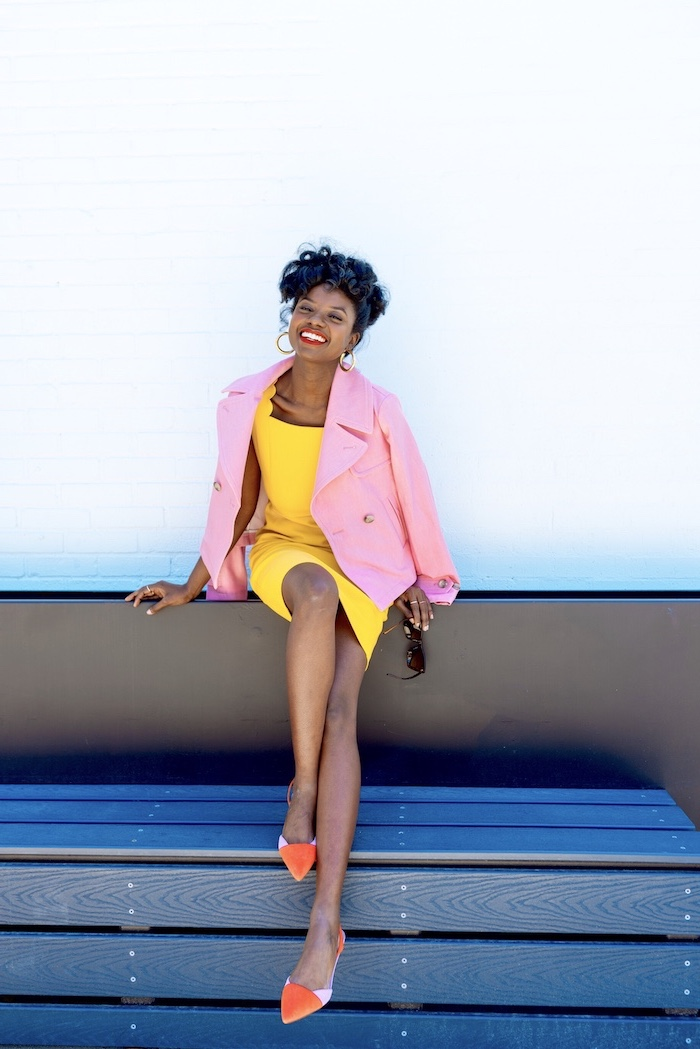 woman with black hair sitting on a bench, wearing yellow drress, easter outfits, pink blazer and flats