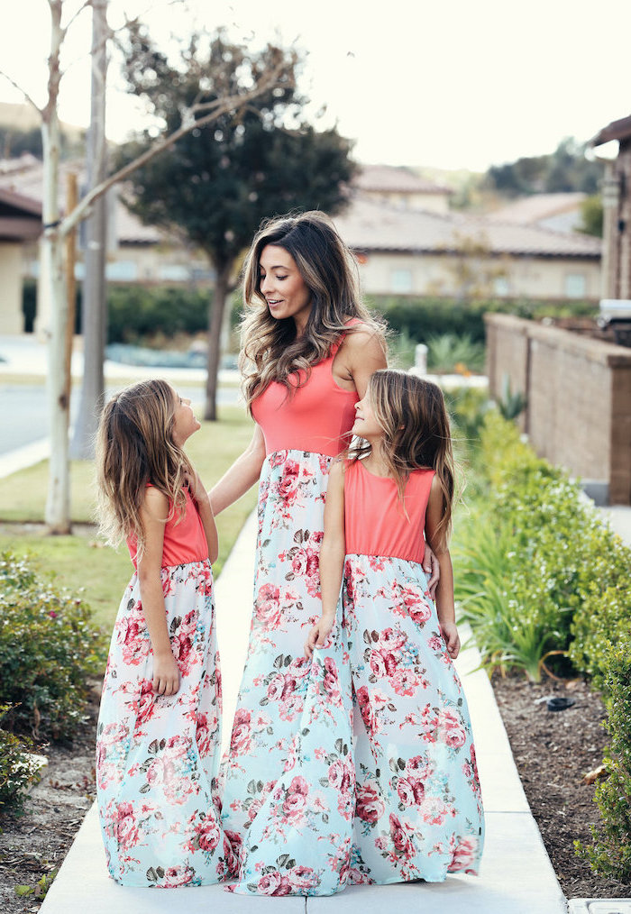 woman standing on a side walk with two girls, wearing identical dresses with floral prints, easter outfits