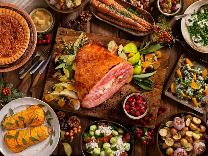 large piece of meat on wooden cutting board, surrounded by different meals, easter dinner recipes, buffet table