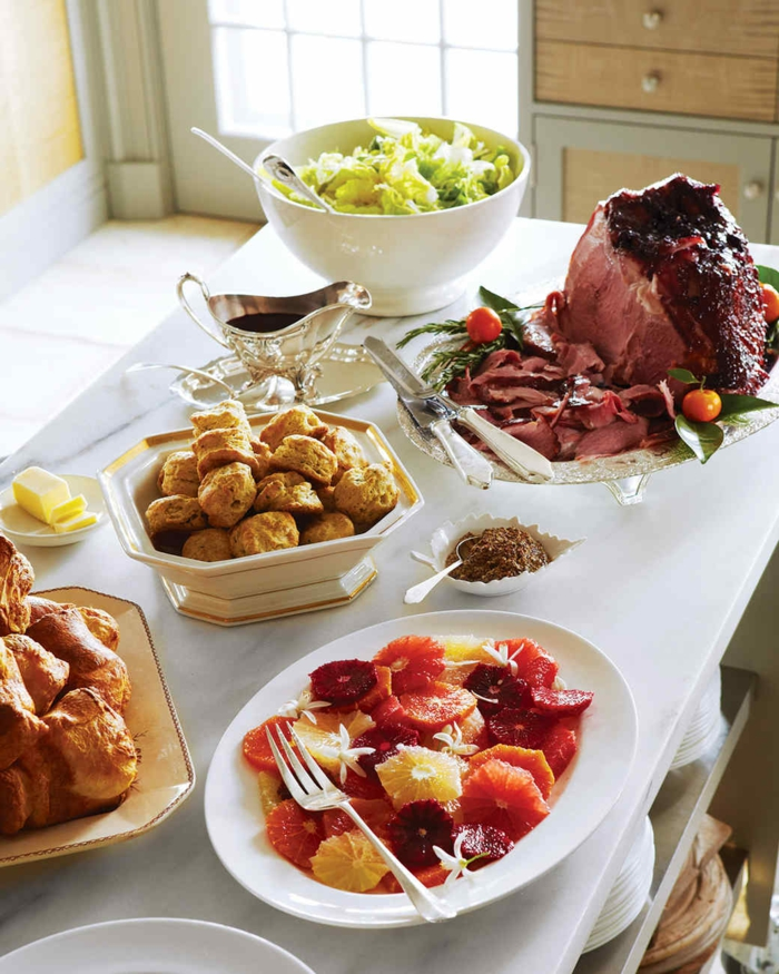 white table filled with plates and bowls, large piece of ham and bread, salad and fruits, easter lunch ideas