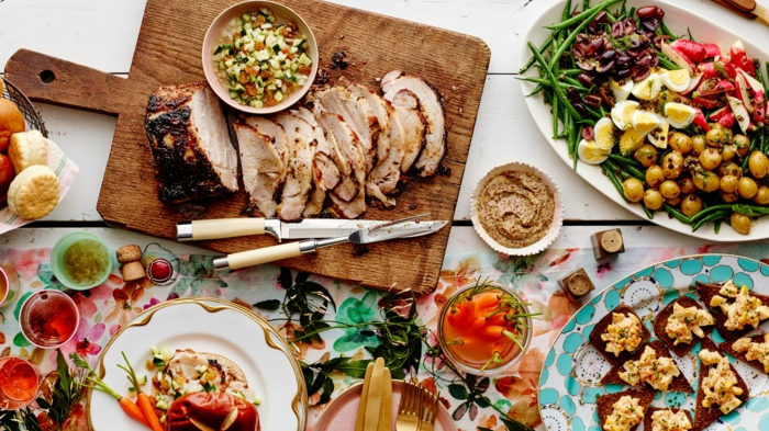 buffet table, sliced ham on a wooden cutting board, easter lunch ideas, surrounded by white plates with different side dishes