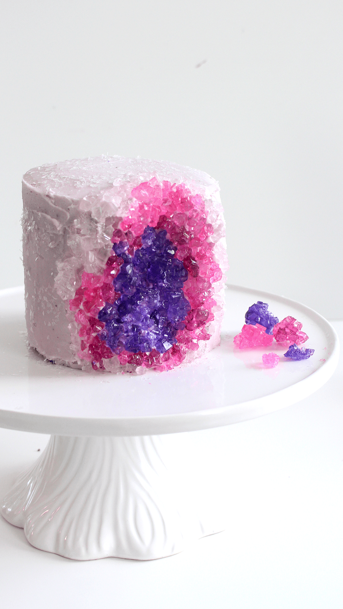 one tier cake, covered with white buttercream, decorated with pink and purple rock candy, geode wedding cake, placed on white cake stand