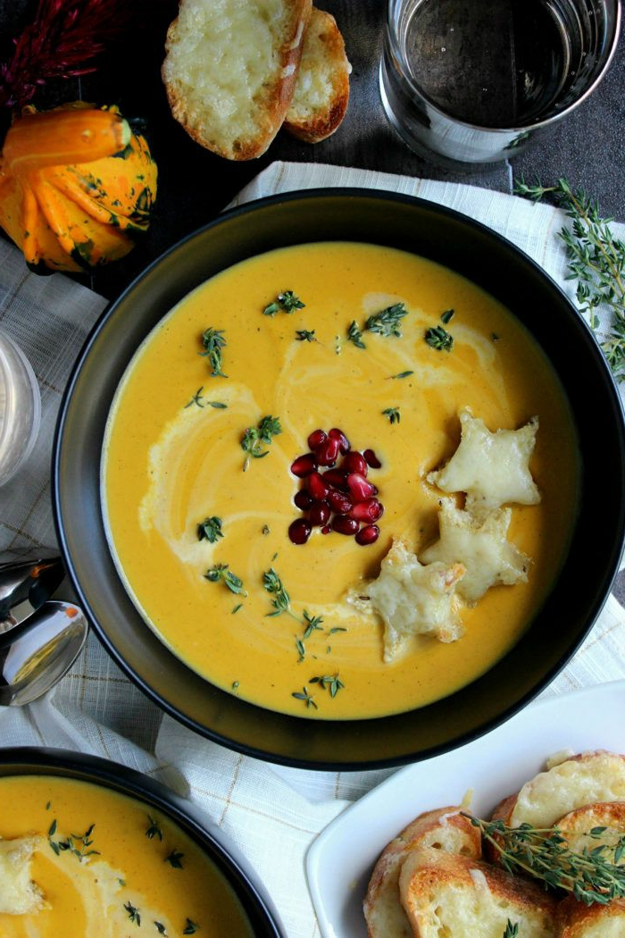 butternut squash soup, garnished with pomegranate seeds, dinner ideas for tonight, poured in black bowl