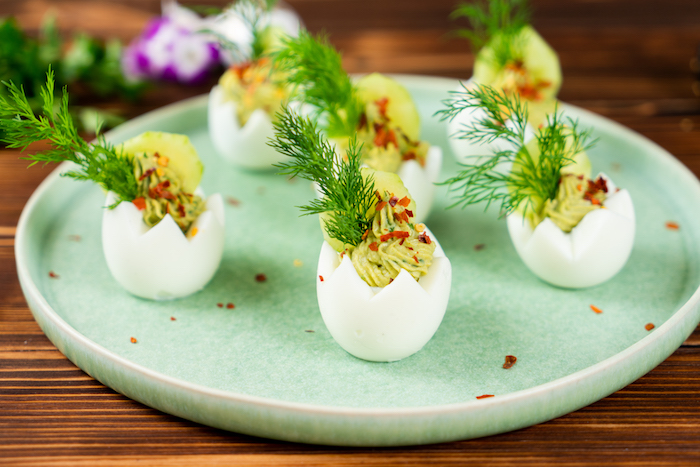 carved out egg whites filled with egg yolk mixture easter eggs arranged on green plate decorated with cucumber dill