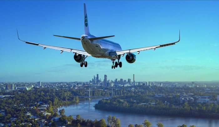 airplane flying low over a river, cheapest flights, city skyline in the background during the day