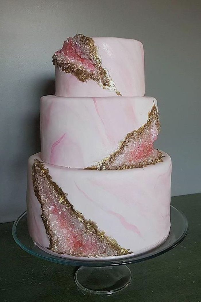 three tier cake, covered with pink and white marble fondant, decorated with pink and gold rock candy, geode wedding cake