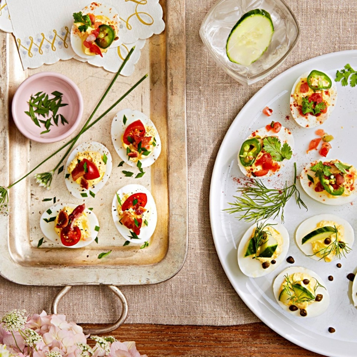 deviled eggs with different garnishes, halved cherry tomatoes and cucumbers, easter lunch ideas, arranged on two plates