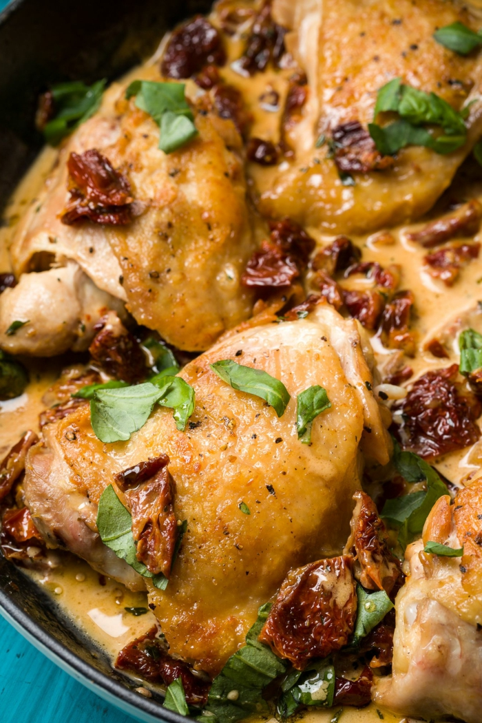easy dinner recipes for beginners, chicken thighs baked in iron skillet, fresh basil leaves for garnish