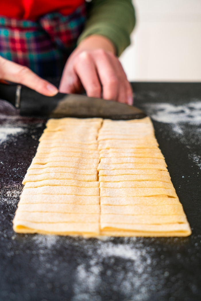 dough being cut into thin strips, placed on black surface covered with flour, tagliatele recipe