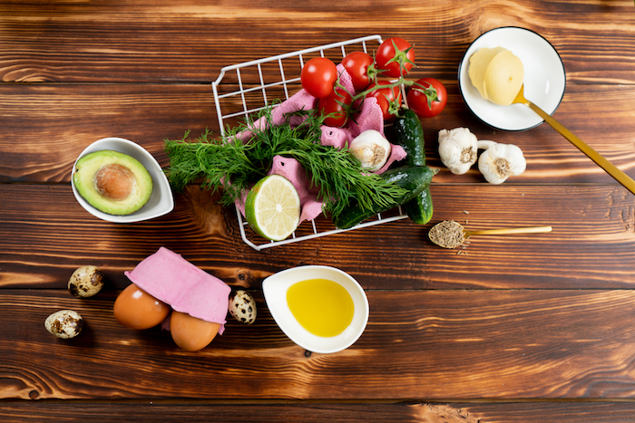 easter dinner ideas stuffed eggs with avocado mustard cucumbers ingredients laid out on wooden surface