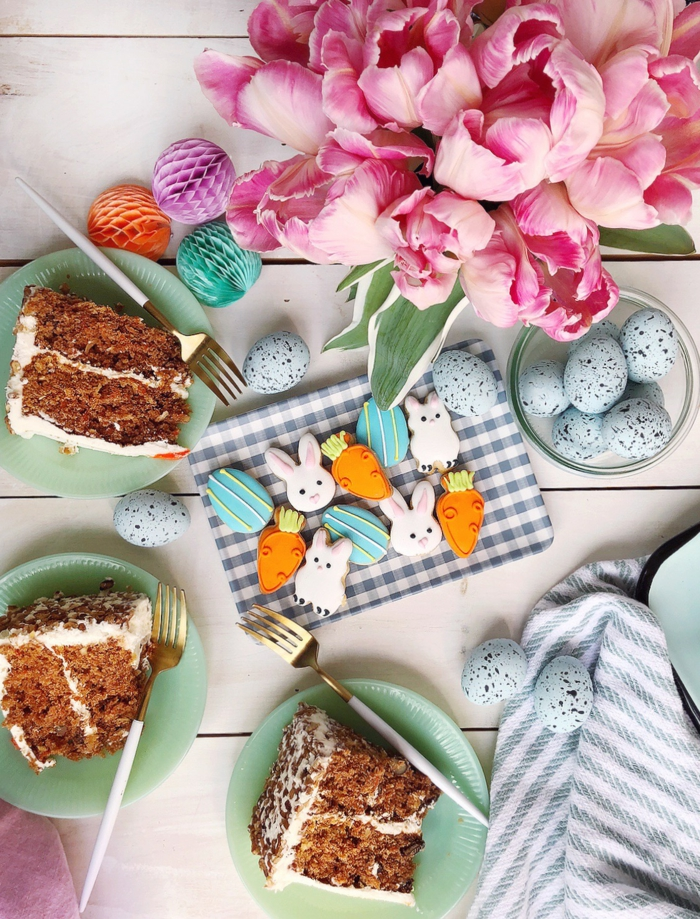 easter dinner ideas, white wooden table, plates with slices of carrot cake on it, bunny shaped cookies