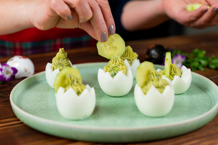 easter eggs being carved out filled with mixture decorated with cucumber slices arranged on mint green plate