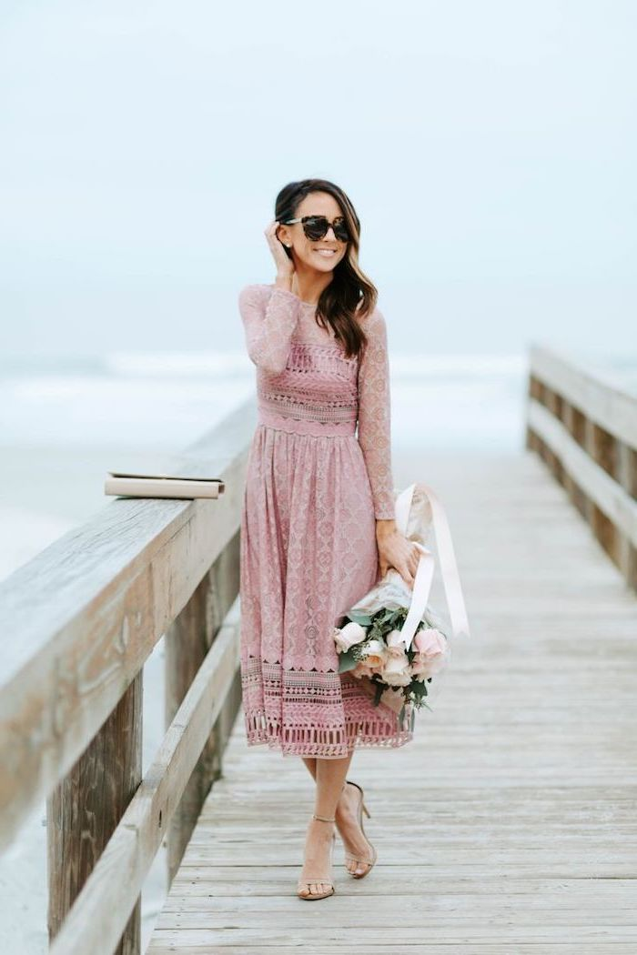 woman with brown wavy hair, wearing a blush pink lace dress, easter outfits women, holding a bouquet of roses