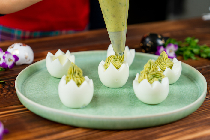 egg whites boiled carved out easter dinner ideas filled with mixture with piping bag placed on green plate
